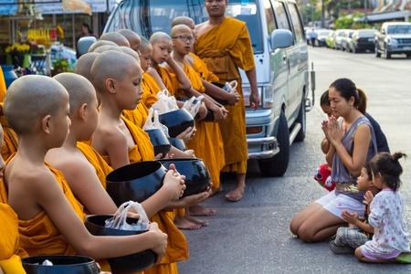 limosna: j�venes monjes budistas caminando limosna recogida de las mujeres y su duagther de la ma�ana, Bangkok, Tailandia