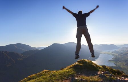 sky diving: A man jumps off a the edge of a mountain.