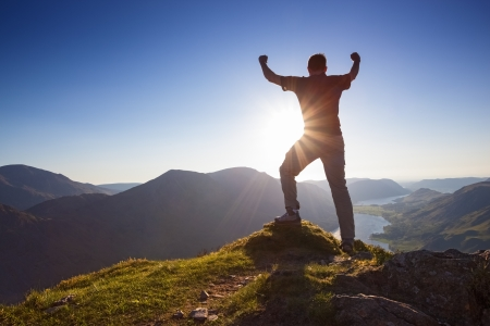summit: Man celbrating with arms stretched in the air on the summit of a mountain
