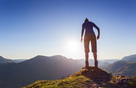 A woman on the edge of a mountain Contemplating jumping off. Stock Photo