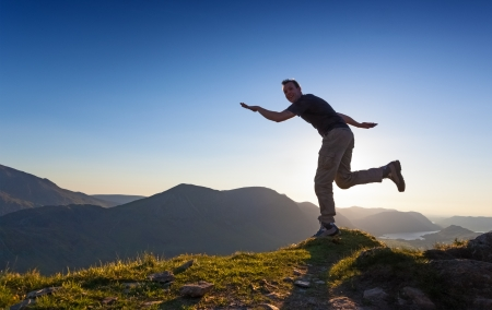 cumbria: A man makes a comical move as if to dive off the mountain. Stock Photo