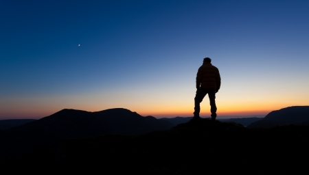 A man takes stock of what he has achieved after reaching the summit Stock Photo