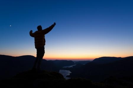 Um homem celbrates no cume de uma montanha Banco de Imagens