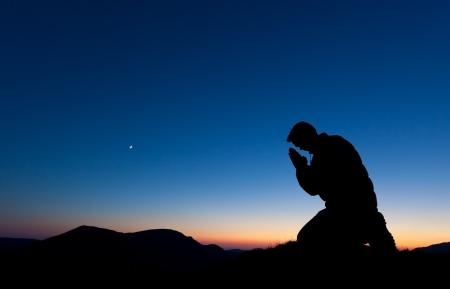 inginocchiarsi: Uomo che prega sulla cima di una montagna al tramonto con la luna nel cielo. Archivio Fotografico