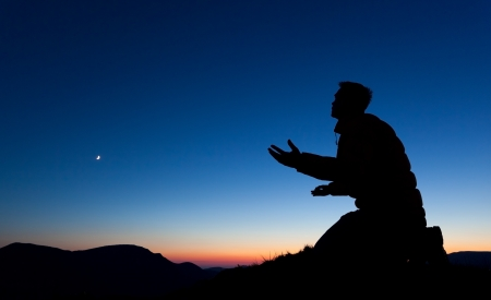 kneeling: Man pleading on the summit of a mountain at sun set with the moon in the sky.