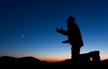perdonar: El hombre rezando en la cima de una montaña en la puesta de sol con la luna en el cielo. Foto de archivo