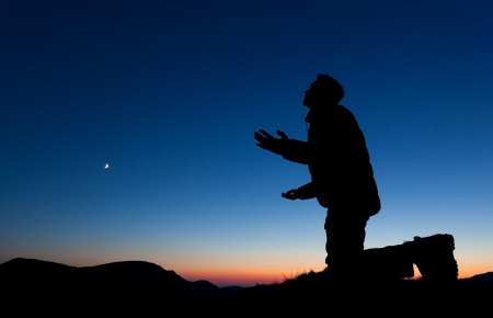 Man praying on the summit of a mountain at sun set with the moon in the sky.