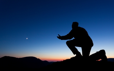 Man praying on the summit of a mountain at sun set with the moon in the sky. photo