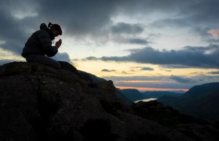 ひざまずく: 山の頂上に神に祈る女性。