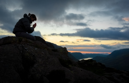 kneeling woman: A woman praying to God on the summit of a mountain.