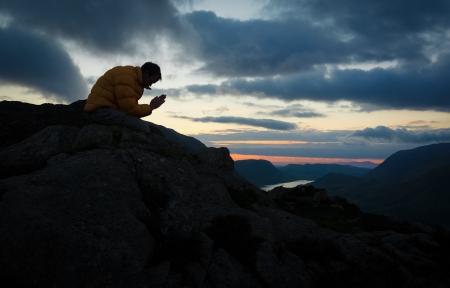 Um homem orando a Deus no cume de uma montanha. Banco de Imagens