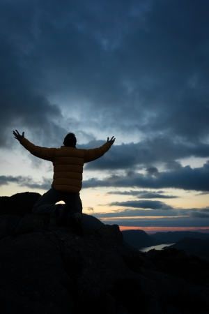 kneeling: A man worshiping God from the summit of a mountain. from the summit of a mountain.