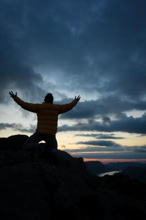 arrodillarse: Un hombre de adorar a Dios desde lo alto de una montaña. desde la cima de una montaña. Foto de archivo