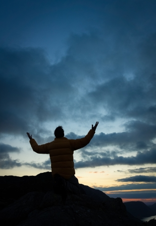 worshiping: A man worshiping God from the summit of a mountain. Stock Photo