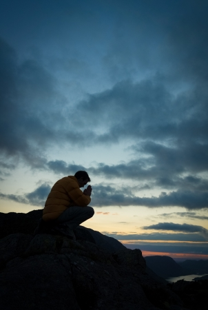 man side view: A man praying to God on the summit of a mountain.