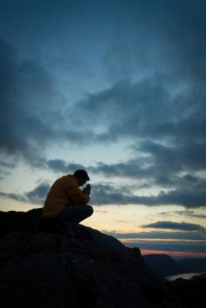 hombre orando: Un hombre que ruega a Dios en la cima de una montaña. Foto de archivo