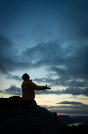 A man pleading to God on the summit of a mountain photo