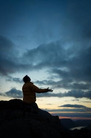 Un hombre suplicando a Dios en la cumbre de una montaña Foto de archivo