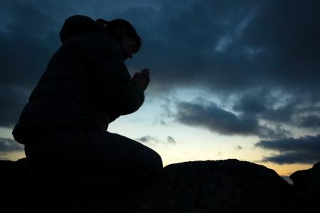 Uma mulher orar a Deus no cume de uma montanha.