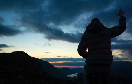 Uma mulher adorando a Deus a partir do cume de uma montanha.