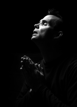 loving hands: High contrast black and white image of a man praying