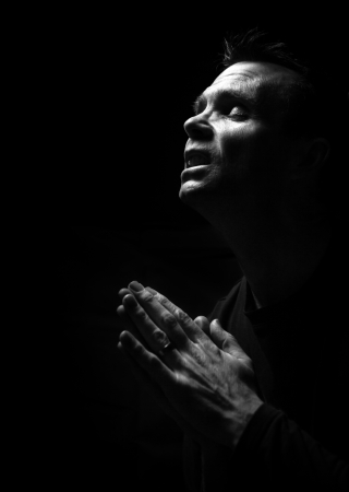 A black and white image of a man kneeling down praying to God  photo