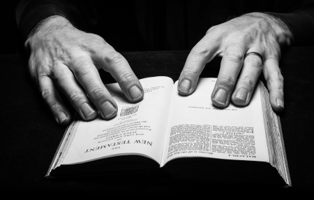 A man reading the Holy Bible with two hands  photo