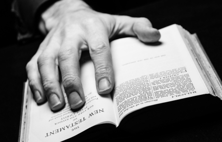 A man reading the Holy Bible with one hand  photo