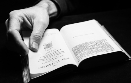 reading bible: A man reading the Holy Bible with one hand