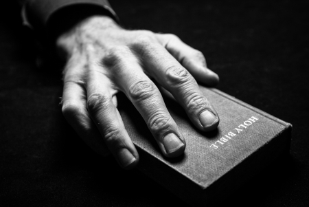 A mans hand holding the Holy Bible  免版税图像