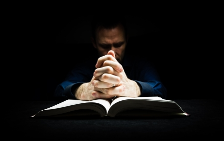 Man praying to God with his hands resting on a bible