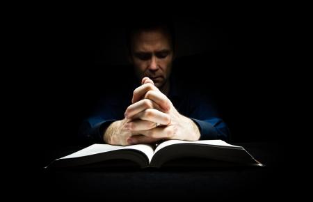 Man, die bidt tot God met zijn handen rustend op een bijbel. Stockfoto