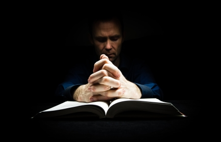 in loving memory: Man praying to God with his hands resting on a bible.