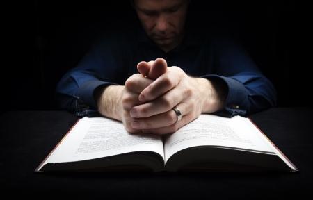 hombre orando: Hombre rezando a Dios con las manos apoyadas en una biblia.