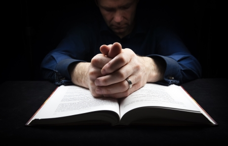 Man praying to God with his hands resting on a bible. photo
