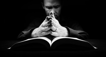 loving hands: Man praying to God with his hands resting on a bible.