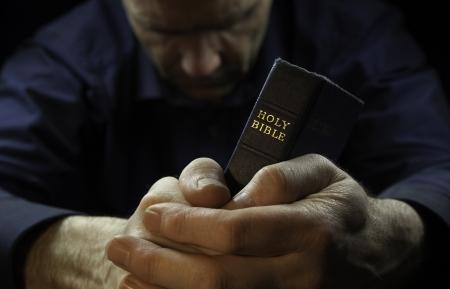 Een man, die bidt met een Heilige Bijbel.