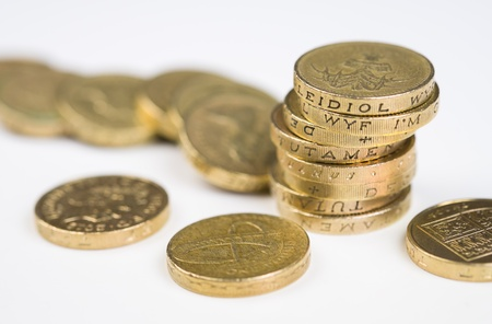 pound coin: A a toppled pile of pound coins on a table.