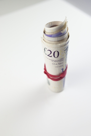 A roll of twenty pound notes on a table. photo