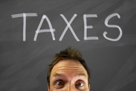 Mans head with a taxes message on a blackboard