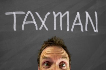 taxman: Mans head with a taxes message on a blackboard