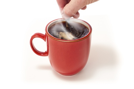 stiring: Hand stiring a red mug of coffee on a white isolated background. Stock Photo
