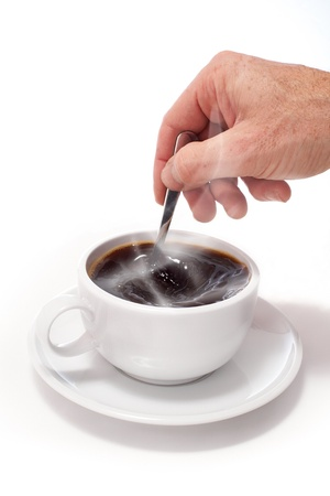 Hand stiring a white cup of coffee on a white isolated background. photo