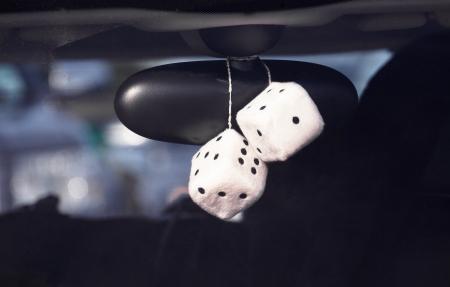 Pluizige dobbelstenen opknoping van de achteruitkijkspiegel van een auto, boy racer stijl Stockfoto