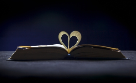 An open Bible with the pages forming the shape of a heart on a table. photo