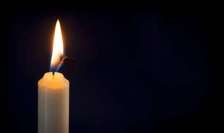 A single lit candle on a dark background.