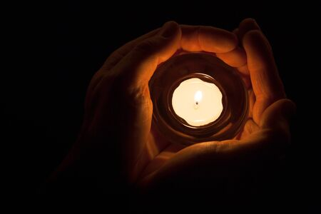 Hands Cupped around a Lit Candles