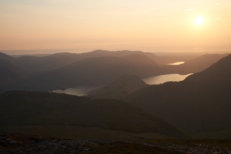 The sun setting behind the mountains in the English Lake District. Stock Photo - 22384865