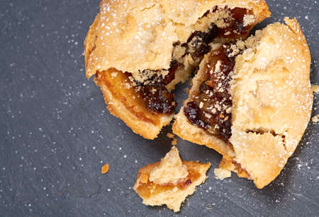 A broken sweet Christmas mince pie on a Slate cooling board  Stock Photo