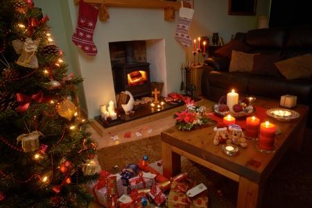 Een kerstboom scene 's nachts met aangestoken kaarsen en vuur.